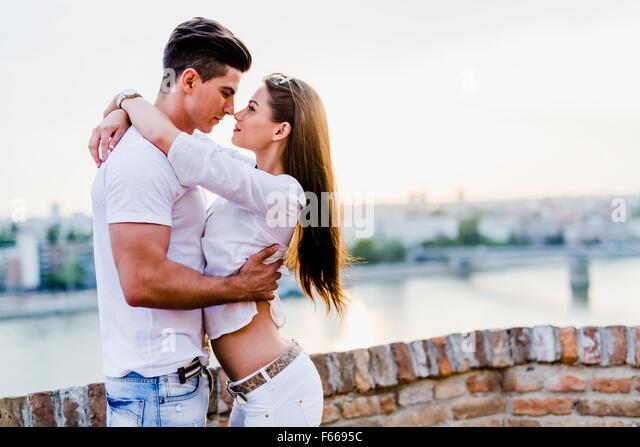Romantische Pärchen umarmen und küssen in wunderschönen Sonnenuntergang über Stockbild