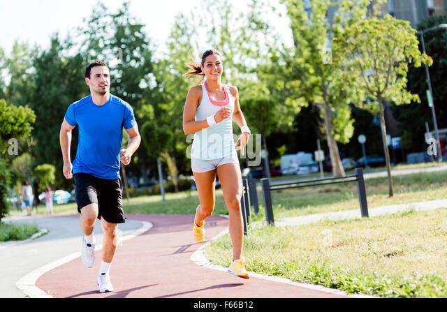 Ein Mann und eine Frau auf einem Stadtkurs Joggen Stockbild