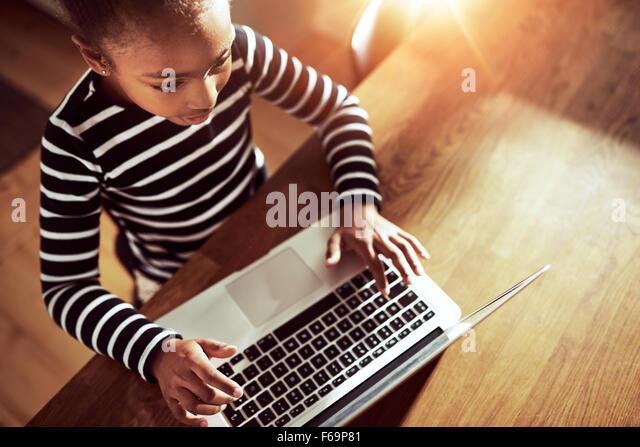 Ethnische schwarze Mädchen sitzen am Esstisch zu Hause auf einen Laptop-Computer, erhöhte Ansicht Blick Stockbild