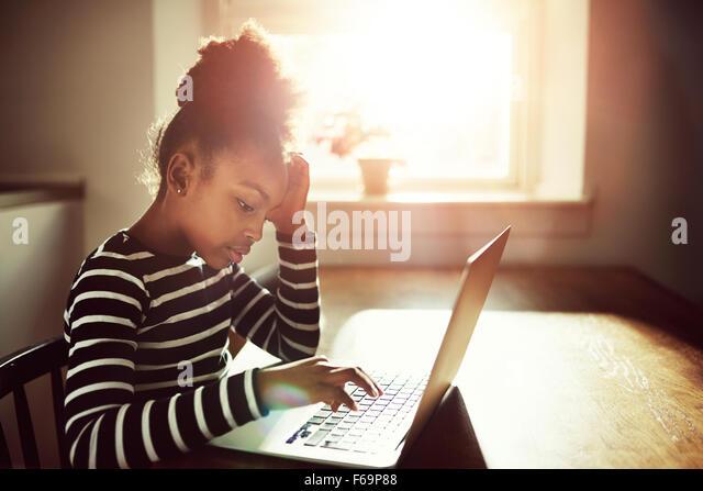 junge schwarze Mädchen arbeiten auf ihre Hausaufgaben zu Hause Eingabe von Informationen auf einem Laptopcomputer, Stockbild