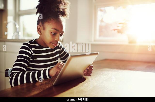 Junge schwarze Mädchen mit einem lustigen Afro Frisur sitzt an einem Tisch zu Hause Surfen im Internet auf Stockbild
