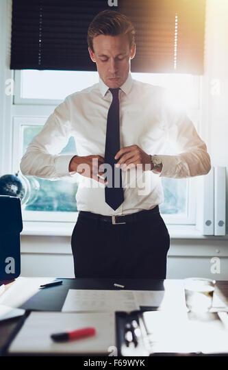 CEO executive Business Typ weiß männlich bindet seine Krawatte stehend am Schreibtisch in seinem Büro, Stockbild