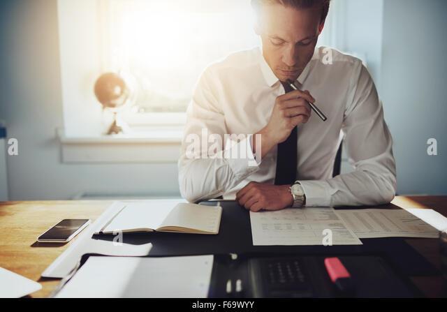 Ernsthaften Geschäftsmann arbeiten an Dokumenten, die auf der Suche konzentriert mit Aktenkoffer und Telefon Stockbild