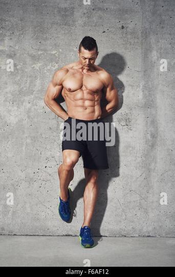 Fitness Modell vor grauem Hintergrund stehend, kein Shirt, Bauchmuskulatur, Nahaufnahme, Fitness Concept Werbung Stockbild