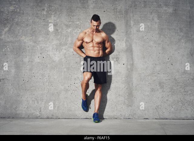 Fitness Modell stehend gegen grauen Hintergrund, kein Shirt, Abdominal- Muskeln, Raum für Raum, Fitness Concept Stockbild