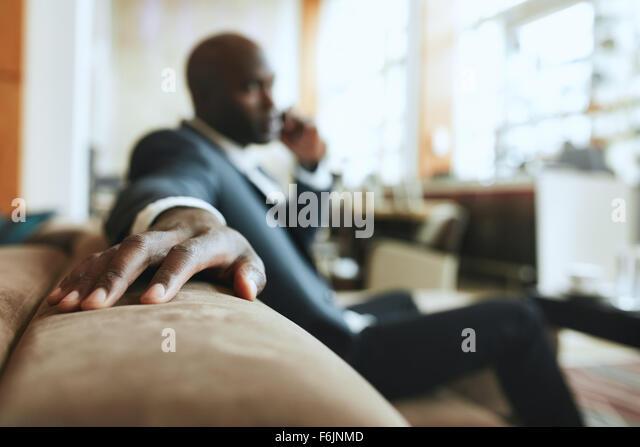 Afrikanischen Geschäftsmann im Lounge-Bereich an der Hotelrezeption telefonieren mit Handy, Fokus auf Seite Stockbild