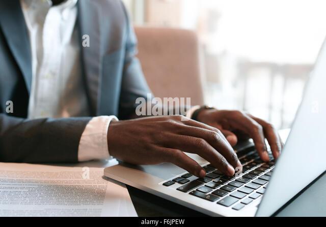 Geschäftsmann, arbeiten am Laptop mit einige Dokumente auf Tabelle. Hautnah auf männliche Hände auf Stockbild