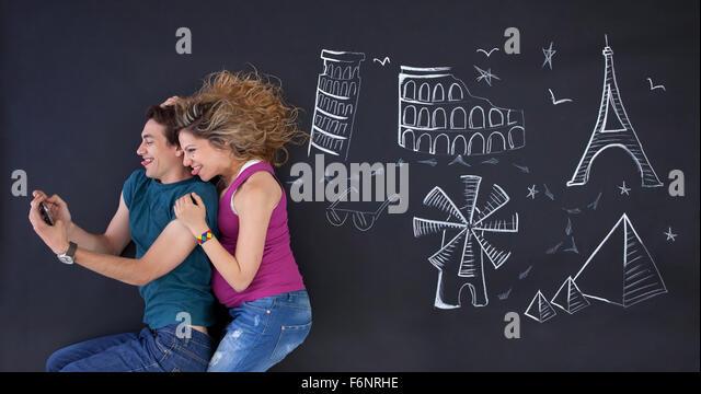 Junges Paar macht ein Selbstporträt mit Welt Attraktionen Buchdrucks hinter. Stockbild