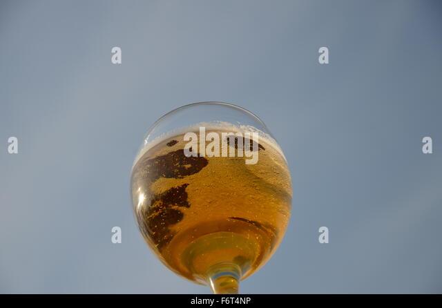 goldenen Perlen in ein Glas Bier auf dem Hintergrund des blauen Himmels Stockbild