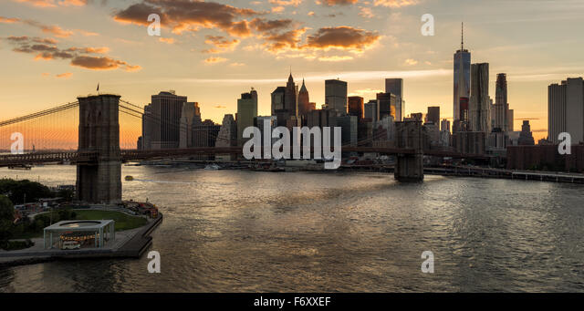 Lower Manhattan Wolkenkratzer und Financial District Skyline bei Sonnenuntergang mit der Brooklyn Bridge über Stockbild