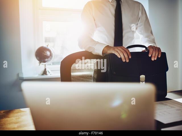 Geschäftskonzept, Mann am Schreibtisch mit Aktenkoffer und Laptop in einem klassischen Business-outfit Stockbild