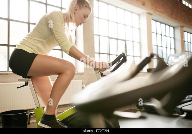 Fit Woman auf Heimtrainer im Fitnessstudio trainieren. Konzentrierte sich junge weibliche trainieren auf dem Fahrrad Stockbild