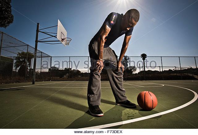 Ein Basketball-Spieler nimmt eine Auszeit aus dem Spiel. Stockbild