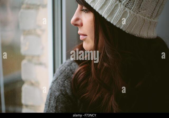 Mädchen in einer Kappe sieht aus dem Fenster. - Stock-Bilder
