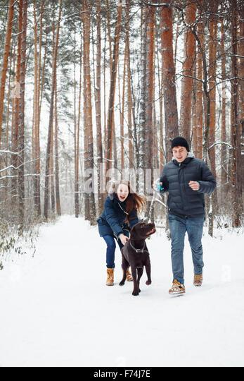 Junges Paar mit einem Hund Spaß im Winterwald auf Urlaub. Selektiven Fokus. Lebensstil der modernen Familienglück. Stockbild