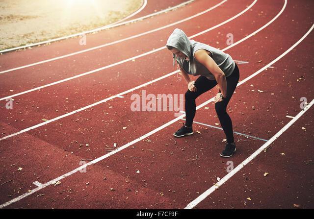 Junge weibliche Läufer im Stadion stehen und Musik hören, entspannen nach dem laufen Stockbild
