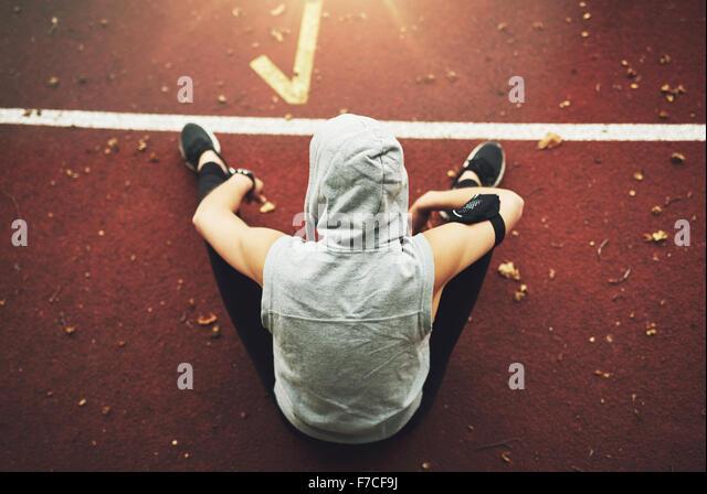 Zurück Blick auf die junge Frau in Sportkleidung sitzen auf Track-Feld und Vorbereitung vor dem Training. unkenntlich. Stockbild