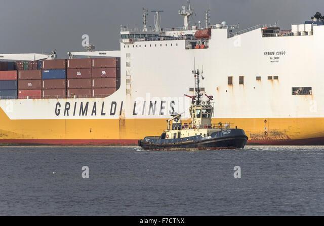 Der Schlepper, die Svitzer Cecilia in den Schatten gestellt durch die großen Containerladung ist Schiff Grande Stockbild