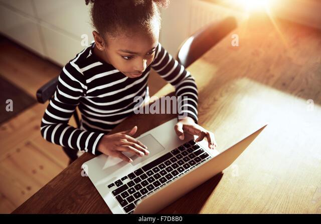 Hohe Betrachtungswinkel von oben auf eine nette junge afrikanische Mädchen, das Surfen im Internet mit einem Stockbild