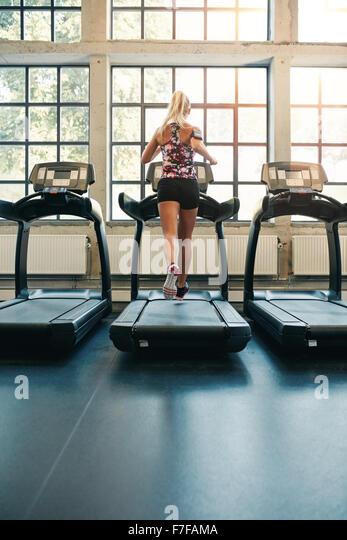 Rückansicht des jungen weiblichen läuft auf Laufband im Fitnessstudio. Fitness-Frau Joggen drinnen im Stockbild