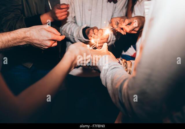 Schuss von Wunderkerzen in Händen von Jugendlichen hautnah. Beste Freunde feiern Silvester Wunderkerzen, in Stockbild