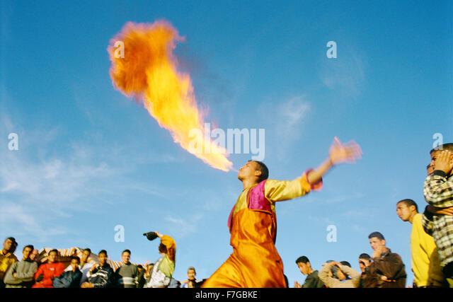 Eine Verschnaufpause Feuer spuckt Feuer auf Jema al-Fna wie eine Menschenmenge blickt auf. Marrakesch, Marokko, Stockbild