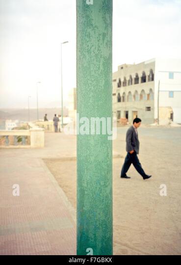 Ein marokkanischer Mann geht auf der anderen Straßenseite hinter einer Straßenlaterne Pol. Sidi Ifni, Stockbild
