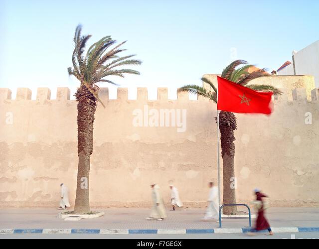 Marokkanische muslimische Männer gehen zügig vorbei an der Stadtmauer auf seinem Weg zum Morgengebet. Stockbild