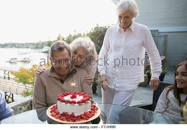 Frau umarmt Mann mit Erdbeer Geburtstag Kuchen Terrasse Stockbild