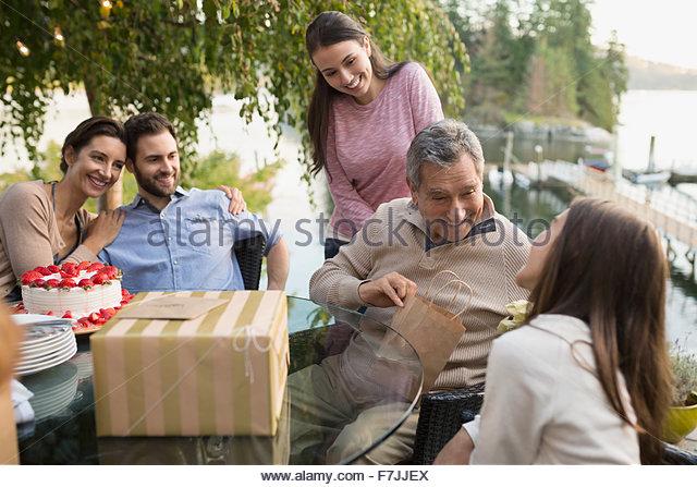Senior woman Geburtstagsgeschenke auf See Terrasse öffnen Stockbild