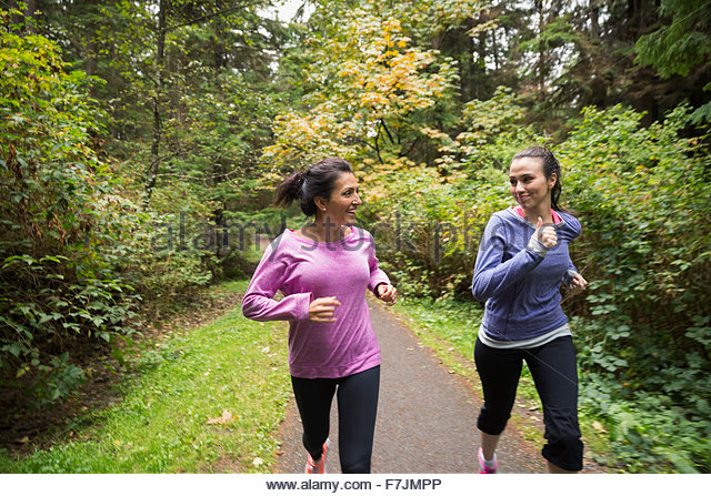 Mutter und Tochter Weg im Wald joggen Stockbild