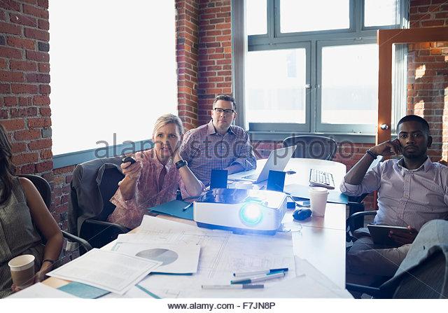 Geschäftsleute mit Projektor in Zimmer Tagung Stockbild