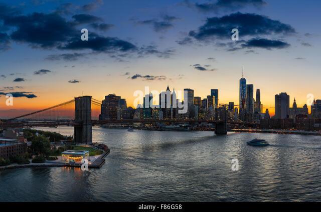 Erhöhten Blick auf die Brooklyn Bridge, East River, Lower Manhattan, Wolkenkratzer und Wolken bei Sonnenuntergang. Stockbild
