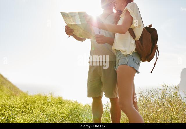 Junges Paar Blick auf Karte von hinten im stehen draußen in der Landschaft mit strahlendem Sonnenschein. Paar Stockbild