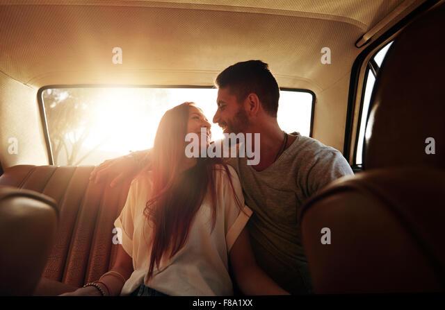 Glückliches Paar Road trip. Junger Mann und Frau sitzen auf der Rückbank des Autos sahen einander lächelnd Stockbild