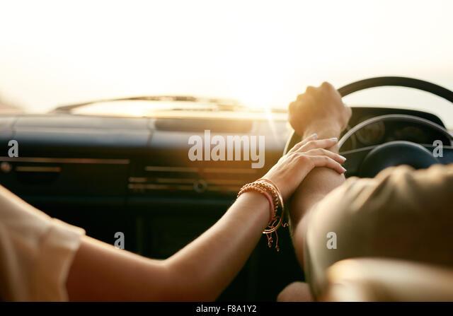 Rückansicht eines jungen Paares, die Hand in Hand beim Sitzen in ihrem Auto zusammen. Mann und Frau auf einem Stockbild