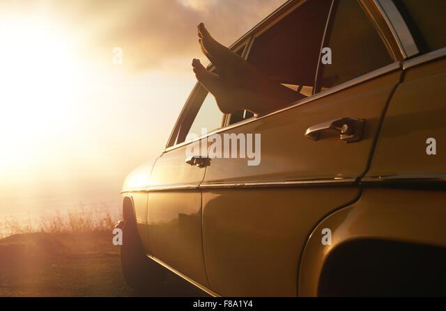 Schuss der Frau in einem Auto auf Reise entspannend. Weibliche Füße hängen aus Fahrzeugscheibe bei Stockbild