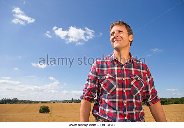 Lächelnd Landwirt in sonnigen ländlichen Gerstenfeld Ernte im Sommer Stockbild