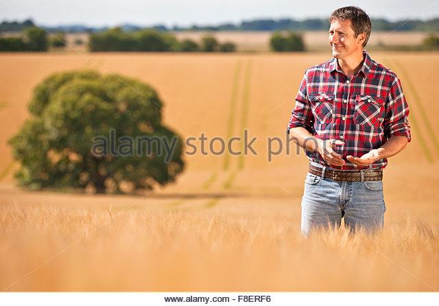 Landwirt in sonnigen ländlichen Gerstenfeld Ernte wegschauen Stockbild