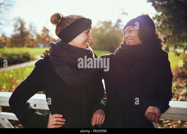Zwei Freundinnen einander an und lächeln suchen, auf der Brücke stehen in Park Stockbild