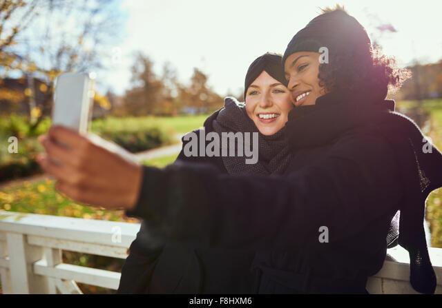 Zwei lächelnde junge Frauen in warme Kleidung dabei selfie vor der herbstlichen Park Stockbild