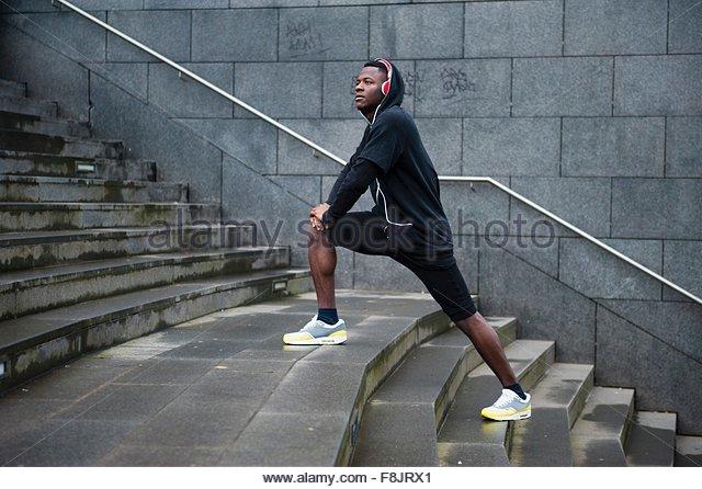 Junger Mann, Training, stretching Beine auf Treppen, im freien Stockbild