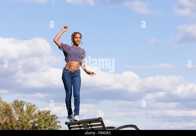Junge Frau trägt Crop Top balancieren auf zurück auf Parkbank Stockbild