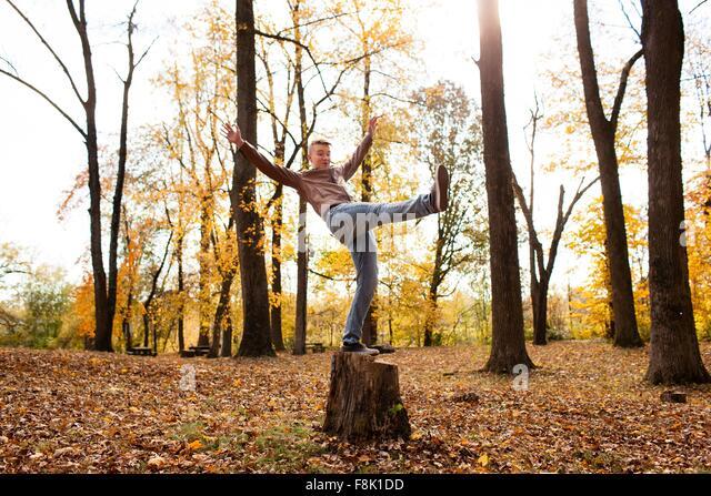 Teenager, balancieren auf Baumstumpf im herbstlichen Wald Stockbild
