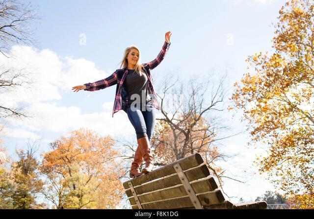 Junge Frau balancieren auf der Parkbank im herbstlichen Wald Stockbild