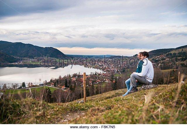Seitenansicht des paar sitzen, Blick auf See, Schliersee, Bayern Stockbild