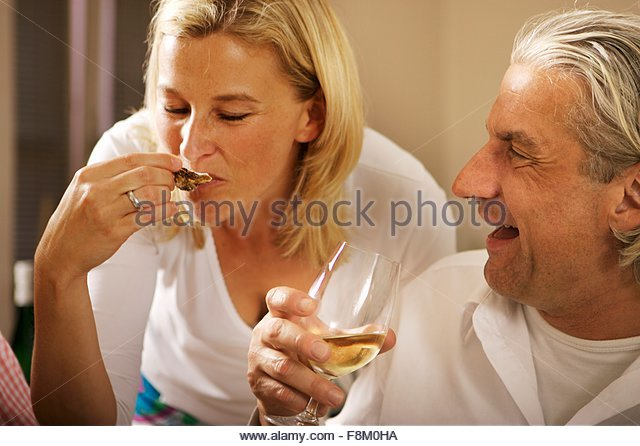 Blonde Frau und grauhaarige Mann auf einer party Stockbild
