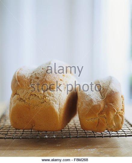 Frisch gebackenes Brot, kleine und große, auf einem Kuchengitter abkühlen Stockbild