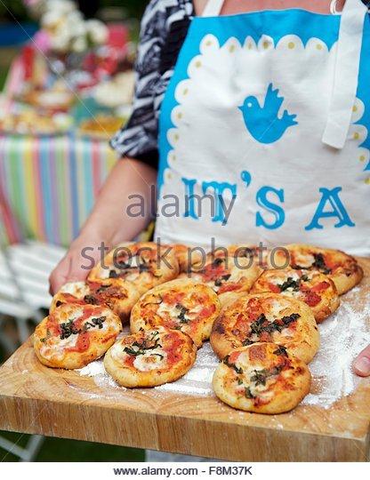 Frau mit Mini-Pizzen auf Holzbrett Stockbild