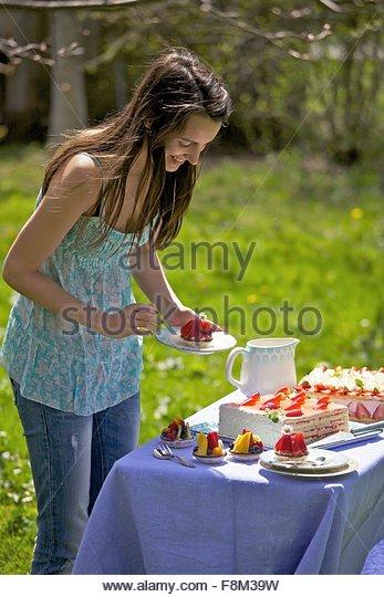 Eine junge Frau von einem Kuchenbuffet im freien Stockbild